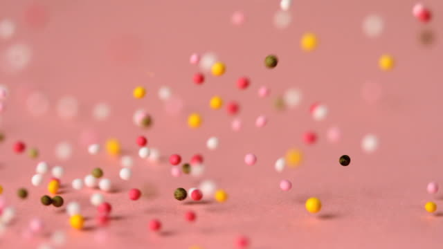 Loads of sprinkles falling on pink surface and rolling across