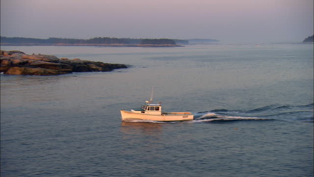 LOW AERIAL, TS, Lobster boat in Penobscot Bay at sunrise, Maine, USA
