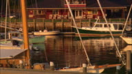 MS, Lobster boat passing by sailboats moored in harbor at sunset, Camden, Maine, USA