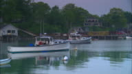 MS, Lobster boats anchored in calm harbor at twilight, buildings and dock in background, New Harbor, Maine, USA