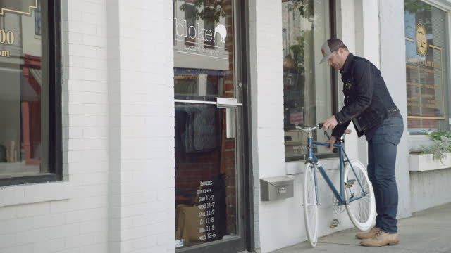Local business owner rides bicycle up to downtown storefront and unlocks shop.