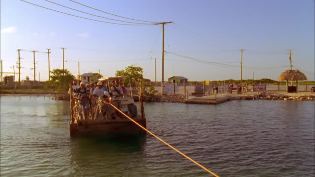 Local man pulls passenger filled water taxi across river using rope and begins to moor craft, Belize Available in HD.