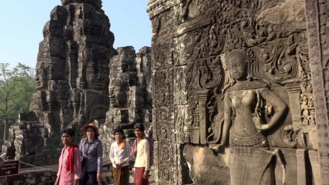 Local people between Apsara relief and giant stone face tower of Bayon temple