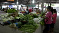 Local people buy vegetables in a covered market