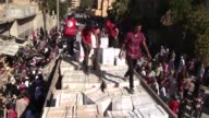 Local residents gather to receive humanitarian aid parcels provided by the Syrian Red Crescent in the northeastern city of Deir Ezzor