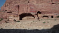 Local riding donkeys in front of the Royal tombs in Petra