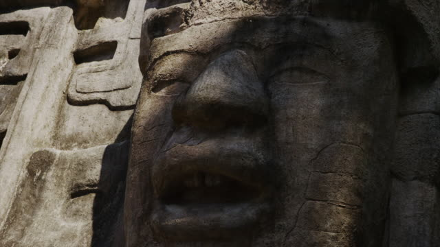Lockdown close up shot of stone face at Mask Temple / Mask Temple, Lamani, Belize,