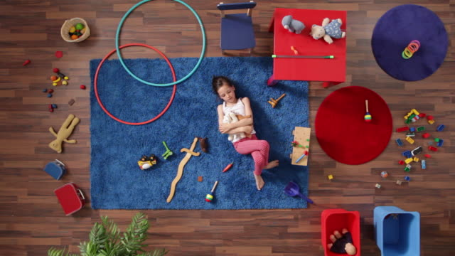 MS, Lockdown, young girl playing in a room with a lot of toys, overhead view