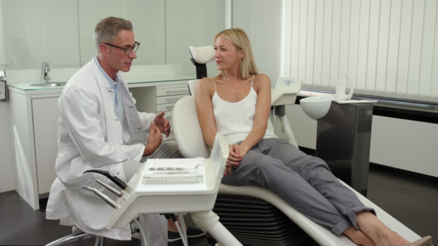 Dentist's office - mid adult dentist doctor with short greying hair in white medical doctor's coat welcomes a female patient woman with long blonde hair with a hand shake and starts describing the dental health treatment surrounded by medical equipment.