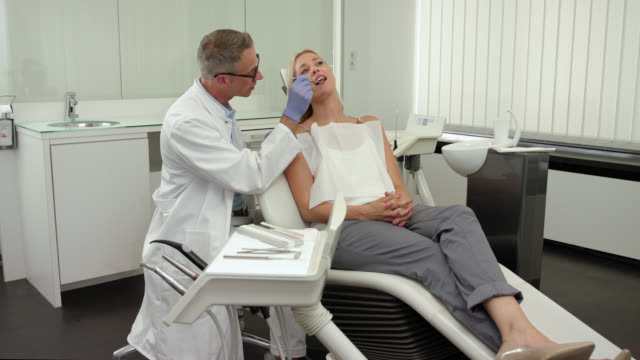 Dentist's office - mid adult dentist with short greying hair and glasses in white medical doctor's coat - female patient with long blonde hair on the chair, doctor starting the dental medical exam of the teeth and mouth with a angled mirror wearing gloves