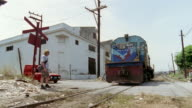 MS, PAN, Locomotive passing camera, people and car crossing railway tracks, Havana, Cuba