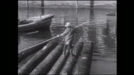 A logger makes a log raft and then uses a pole as he floats the raft under a bridge.