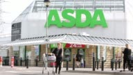 Logos sit on the handles of shopping carts outside an Asda supermarket store operated by WalMart Stores Inc in the Wandsworth borough of London...