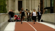 London INT Unidentified man speaking on stage Tyson Gay and Allyson Felix sprinting across the Millennium Bridge