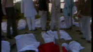 Meredith Alexander resigns from watchdog over Dow Chemical sponsorship 6121984 / AS061284012 EXT People stand looking at bodies on ground covered...