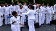 First anniversary Regent's Park Gospel choir singing at service in park SOT Top Shot Woman laying purple carnation in giant flower shape Two women...