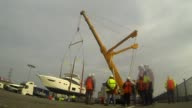 preparations ENGLAND London EXT Boat along river Luxury boats at dock LAPSE footage of boat being lifted out of river by crane and lowered onto...