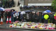 Third attacker and more victims named Close shot flowers and bouquets Close shot message People standing for minute's silence as bongs of Big Ben...