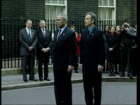 London Downing Street Prime Minister Tony Blair MP and USA Secretary of State Colin Powell from Number 10 past Christmas tree PAN as they stand to...