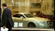 London EXT Back view of besuited man looking at luxury car parked in car showroom Champagne being poured into glasses at Boat Show EXT Suits in...