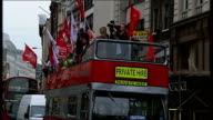London EXT Various views of members of Unite union waving flags from top of openair double decker bus outside TGWU Headquarters in Holborn then along...