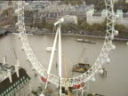 London Eye as wheel rotates and pods are attached river traffic behind; Oct 99