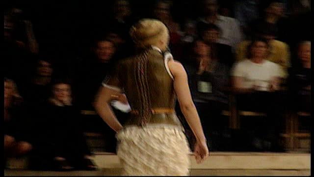 Alexander McQueen LNN MS iv Helena Christensen VS model wearing prosthetic legs modelling a McQueen design LS male model along catwalk wearing pants...