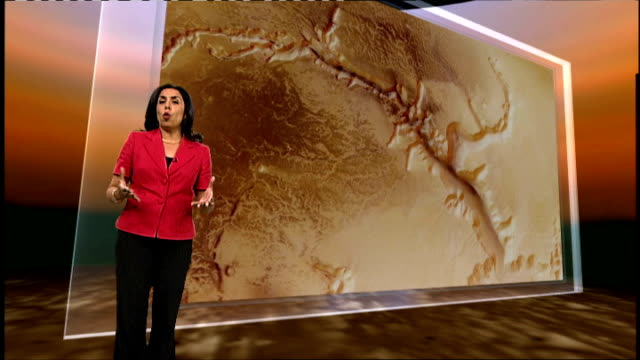 London GIR INT Reporter to camera at video wall showing images of Mars