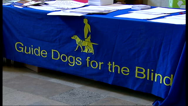 London Guide Dogs 75th year celebrations / general views of people and guide dogs at special church service Table of leaflets covered with blue cloth...