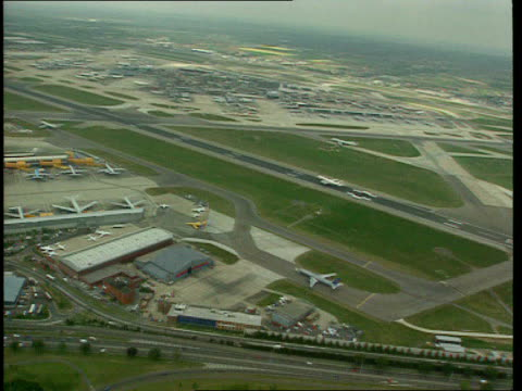 London Heathrow Airport AIR VIEW Planes along runway and starting to take off LIB Planes on tarmac as taxi along TILT UP British Airways plane taking...