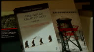 London INT Close Shot of books written by Solzhenitsyn PAN Close Shot of page of 'The Gulag Archipelago' with AUDIO of section being read SOT Cover...