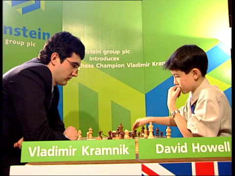 London INT GVs Vladimir Kramnik and David Howell sitting thinking as play game of chess SIDE GV Press crowded around Hands of Howell and Kramnik...