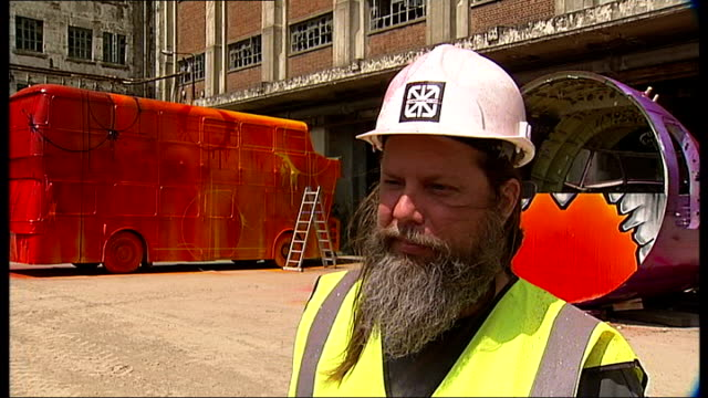 Street artists create artworks at opening RISK interview SOT General views of RISK painting doubledecker bus standing on ladder Derelict building...