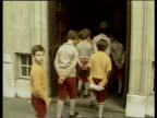 London MS Pupils from Hill House walk along pavement Hill House BV Pupils into school School TS Pupils stand up in assembly PAN RL they sing the...