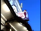 London Shaftesbury Avenue SEQ traffic along theatres DEFOCUSED PULL FOCUS 'Stoll Moss Theatres' sign DUSK GV people standing outside theatre TILT UP...