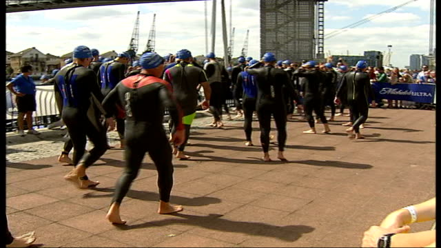 London Triathlon Triathalon competitors along wearing wetsuits PAN Male competitor cycling along DISSOLVE TO Female runner towards DISSOLVE TO Low...
