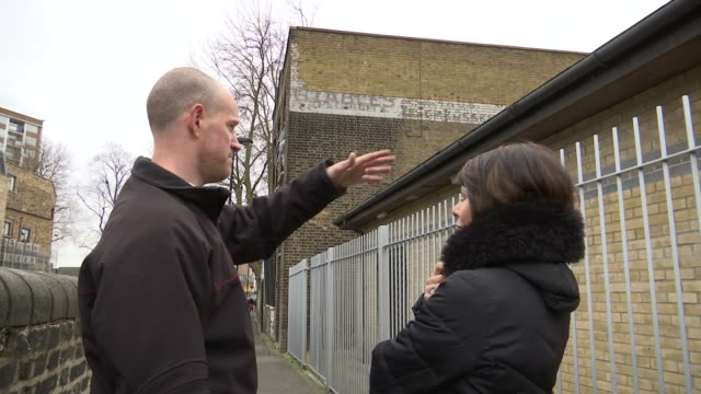 London's ghost signs ENGLAND London Stoke Newington EXT Walls with ghost signs / Reporter and Sam Roberts looking at sign on side of building