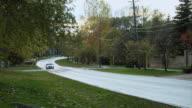 TS Lone car moving along wet, tree lined suburban street / Ontario, Canada