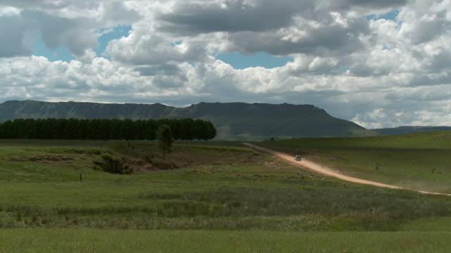 PAN Lone car on dirt road pan of tree lined hilltop to Drakensberg /Pietermaritzburg, Kwa Zulu Natal, South Africa