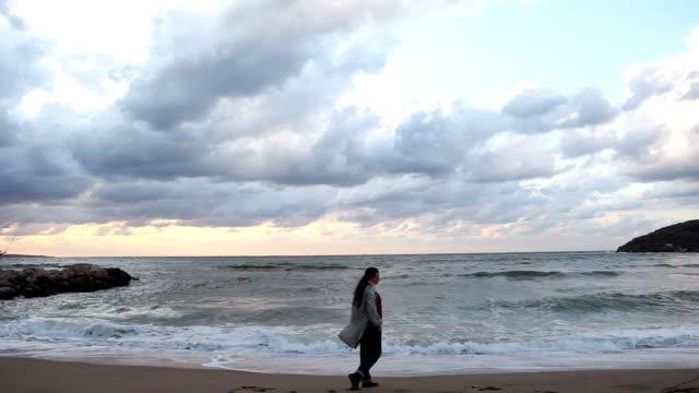 Lonely girl walking, empty beach
