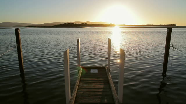 WS Lonely jetty silhouetting against sunrise / Mallacoota, Victoria, Australia