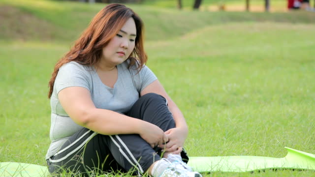 Lonely overweight asian woman in the park