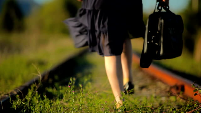 Lonely Woman Walking on Abandoned Railroad Track