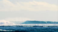 Long 15ft wave breaking along a secluded reef in Indonesia.