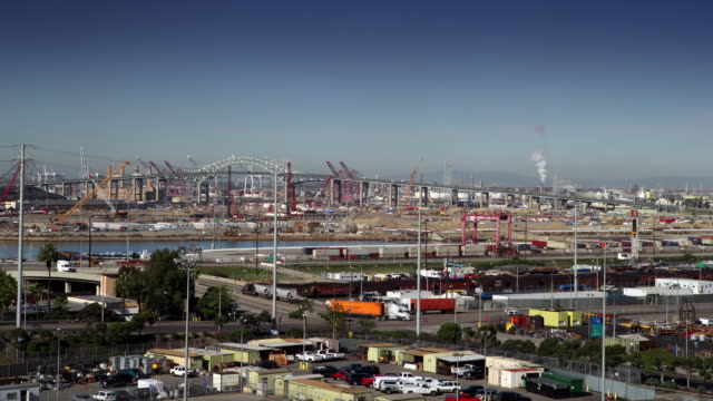 T/L Long Beach Container Terminal and Gerald Desmond Bridge in Long Beach California. Ocean side business activity in the foreground - cranes, containter terminals etc. Midground speeding traffic passing over the bridge