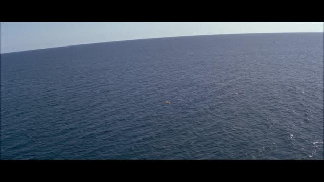MS AERIAL Long down shot of life raft on ocean