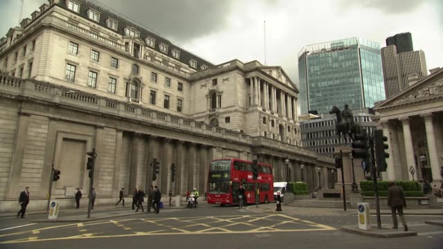 Long duration shot traffic across road junction outside Bank of England and Royal Exchange pedestrians crossing road grey rainclouds in sky Bank of...