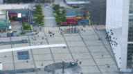 Long focal shot on Parvis de la Défense, with pedestrians and tourists walking in all directions, from elevated view, tilt-shift effect
