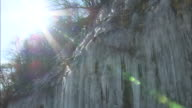 Long icicles hang from a frozen waterfall.