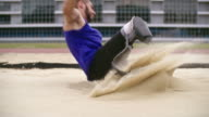 Long jumper with prosthetic leg landing in sand